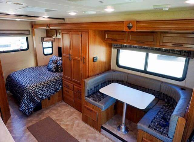 Class B RV buying an RV guide interior photo while in Whitefish Montana just outside of Glacier National Park on our way back from free camping in Telluride Colorado. I have purchased 4 RVs in my lifetime. The latest being a truck camper, but if I were ever to buying an RV again it would be a 20-22 foot Class B RV with a slide just like this one. Plenty of space, u-shaped dining area, full bed, with wardrobe closet! Score. This would be my perfect RV if I were to buy another RV. Which I will because the RV life has me hooked with its freedom, adventures and cheap RV life!
