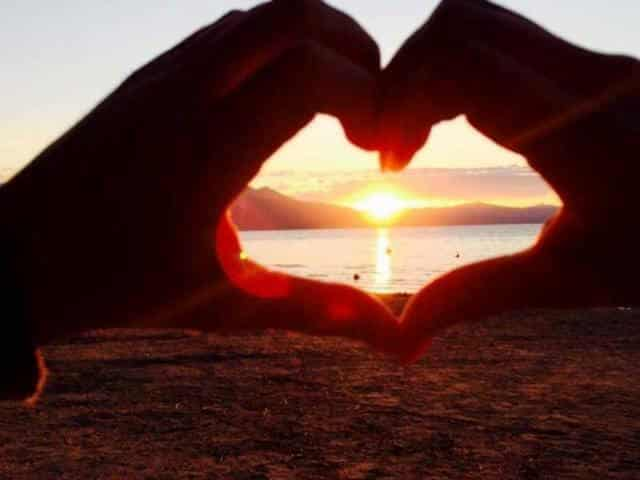 Making heart with hands around sunset in McCall Idaho on the shores of Payette Lake