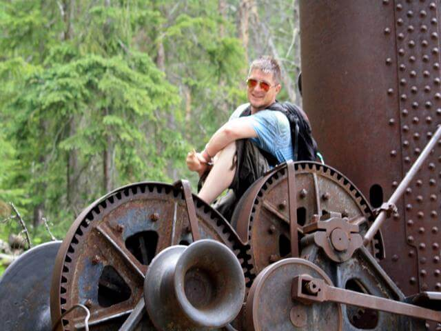 AOWANDERS in Grand Lake Colorado posing for the camera on old mining equipment found along a hiking trail
