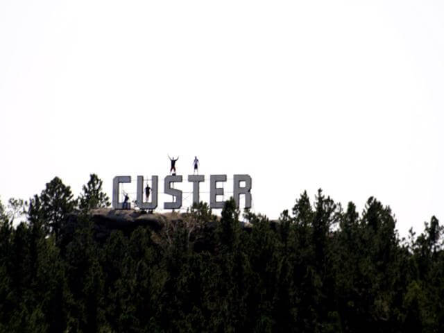 AOWANDERS standing on to of the Custer South Dakota hollywood sign during his first year of full time RV living, and making money working at the buglin bull as a server during Sturgis.